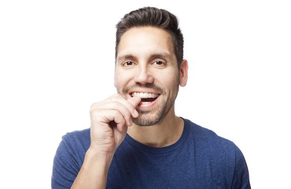 Adult Man With Hand On Teeth Putting In A Retainer